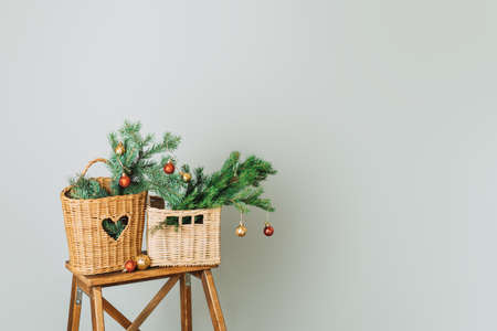 Branches of Christmas tree with bauble in wicker baskets on wooden stepladder.