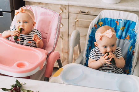 Twins sitting on chairs eating cucumbers.