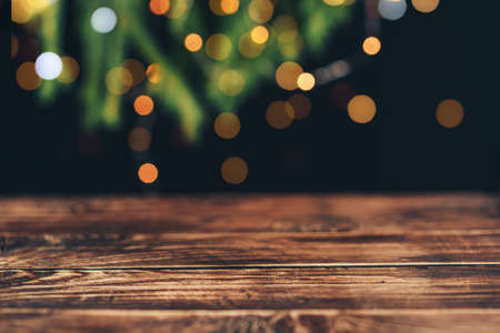 Empty wooden table in front of christmas tree branches with garland.