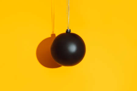 Black matte bauble with hard shadow on yellow background.
