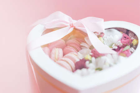 Macarons with flowers of different kinds in a box in the shape of a heart against a pink background. A gift for any occasion. Banque d'images