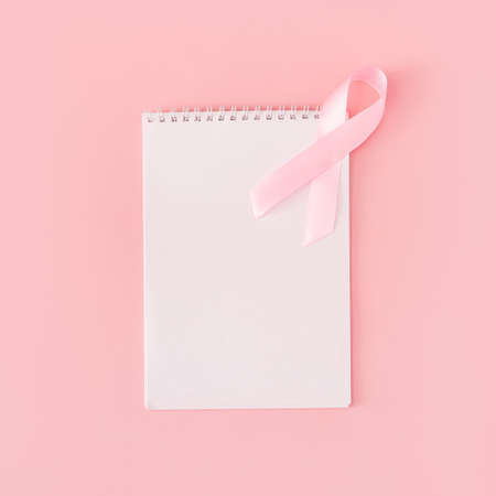 Pink ribbon on white sheet of notepad on pink background.