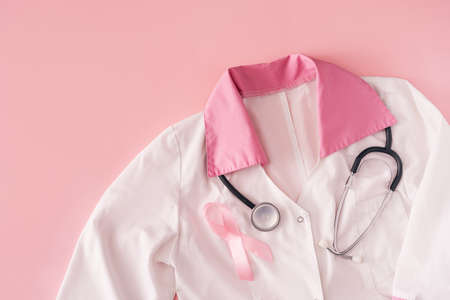 Pink ribbon and stethoscope on white coat on pink background.