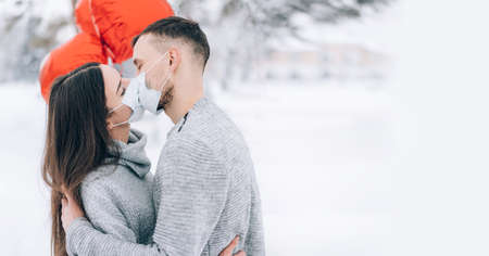 Young couple in love in the park on a background of snow and red heart-shaped balloons. Valentine's day gift. Lovers kiss in medical masks.