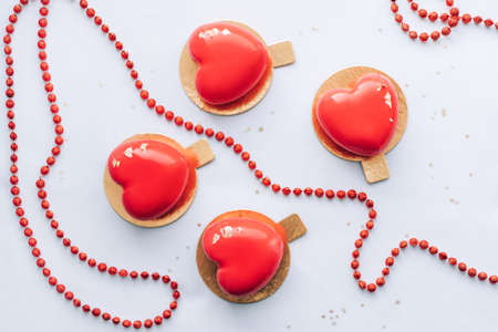 Red heart-shaped cake and red beads. Gift for Valentine's Day and Women's Day. Banque d'images