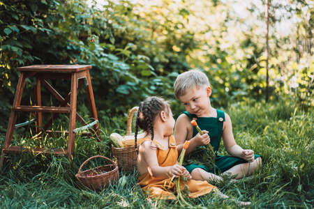 Brother and sister in overalls eating carrots next to basket of vegetables.