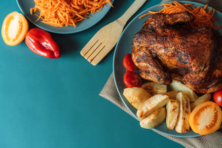 Freshly grilled chicken on blue plate with potatoes and tomatoes on blue background.