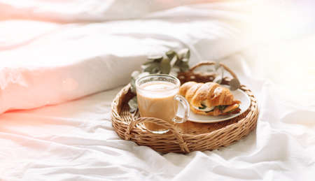 Breakfast in bed with croissant and coffee on tray.