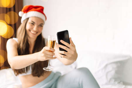 Girl in bed makes selfie with glass of champagne.