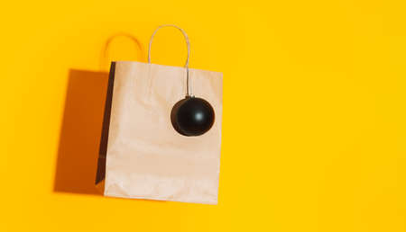 Paper bag with black matte bauble against yellow background.