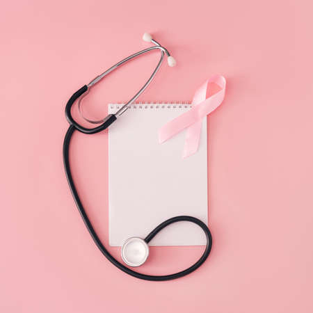 Pink ribbon and stethoscope on white sheet of notepad on pink background. Banque d'images
