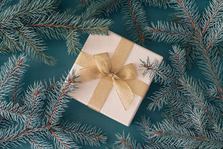 Box with gold ribbon among the branches of Christmas tree on cyan background. Banque d'images