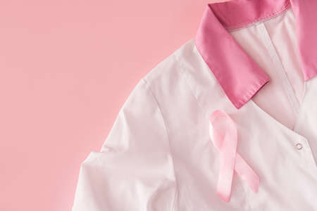 Pink ribbon on white robe on pink background. Banque d'images