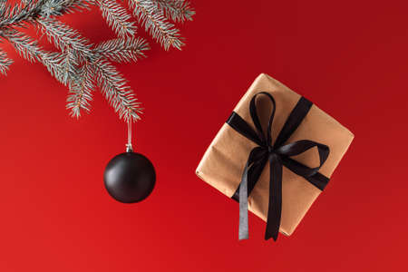 Black matte balls on blue christmas tree branch near gift with black ribbon against a red background. Banque d'images