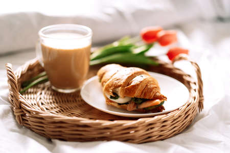 Croissant and coffee on white bed on wicker tray with flowers.