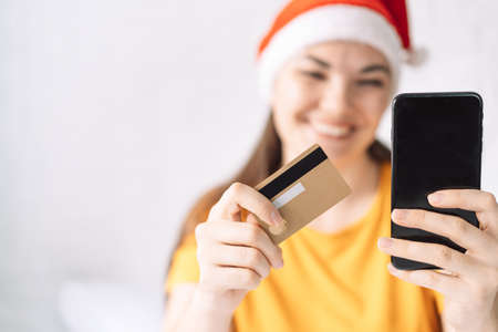 Girl pays for christmas gifts with credit card online. Banque d'images