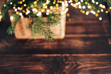Christmas tree branch with garland in basket on wooden table. Banque d'images