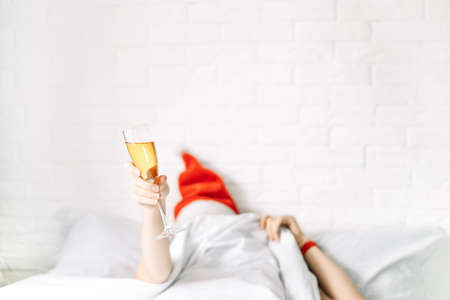Girl in bed raised her hands up holding glass of champagne.