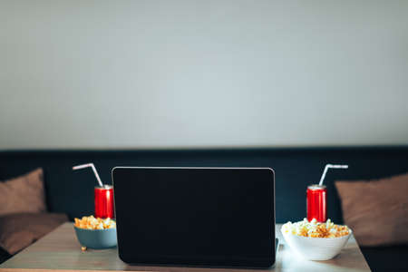 Blank laptop with jars of juice with straws and cups of popcorn.