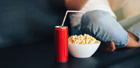 Can of juice with straw and cup of popcorn in front of girl.