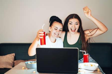 Girls are watching a live broadcast on laptop and rejoice at the victory of their team. Banque d'images