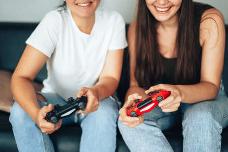 Girls holding joysticks and playing video games.