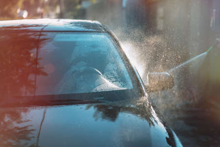 The car is doused with jet of water from hose. Banque d'images