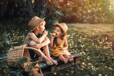 Children in overalls and straw hats eat pear. Banque d'images