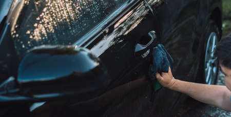 The guy wipes the front door of the car with rag.