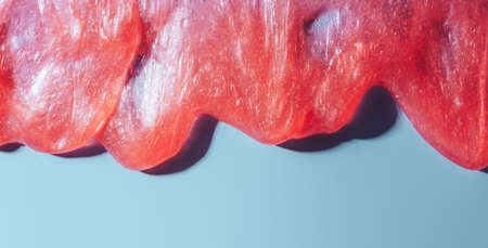 Red liquid slime flowing over blue background.