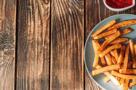French fries on plate next to cup of sauce. Banque d'images