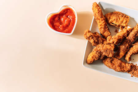 Chicken nuggets on square plate next to heart-shaped cup with tomato sauce.