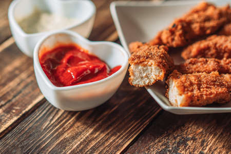 Chicken nuggets on plate next to cup of sauce. Banque d'images