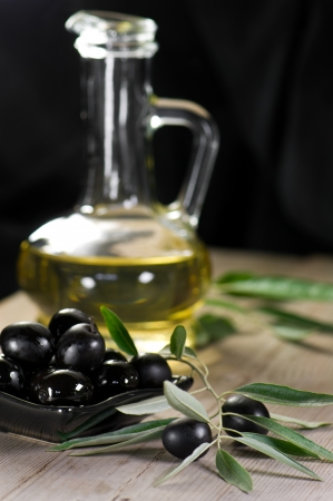 Olives on wood background and olive oil in bottle photo