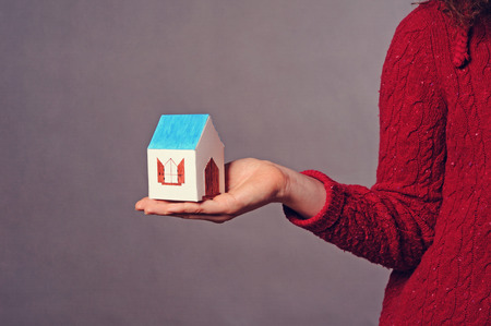 Small House in hand on the gray background photo