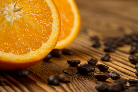 Perfect mix. Cropped closeup shot of a sliced orange and roasted coffee beans on the coffeeshop table.