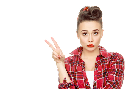 Take two! Young beautiful pinup girl wearing red plaid shirt and vintage makeup showing two fingers or victory sign isolated on white copyspace on the side