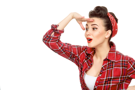 I see an opportunity! Young pin up girl in a plaid red shirt wearing retro hairstyle and red lips makeup looking away happily with her hand to her eyes copyspace on the side
