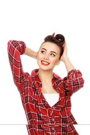 joyfully: Filled with joy. Vertical portrait of an attractive young pinup girl with vintage hairstyle and makeup smiling looking away joyfully fixing her hair with her hands isolated