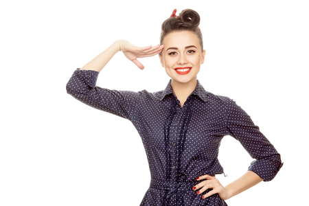 Hey captain! Half length portrait of a gorgeous pinup girl in a dotted dress smiling cheerfully to the camera saluting with her hand isolated on white copyspace on the side