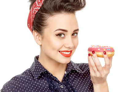 distinct: Boost for happiness. Closeup studio shot of a beautiful pinup girl with a retro hairstyle and makeup holding a delicious donut smiling to the camera isolated on white