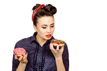 distinct: Hypnotic donut. Stunning retro red lipped pinup woman staring at a donut in her hand hungrily isolated on white copyspace on the side Stock Photo