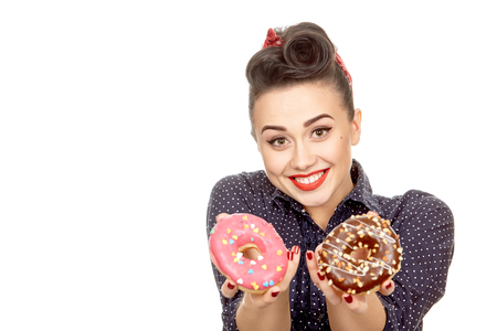 Sweet love. Closeup portrait of a beautiful happy red lipped pinup girl holding delicious donuts smiling joyfully isolated on white copyspace Stock Photo