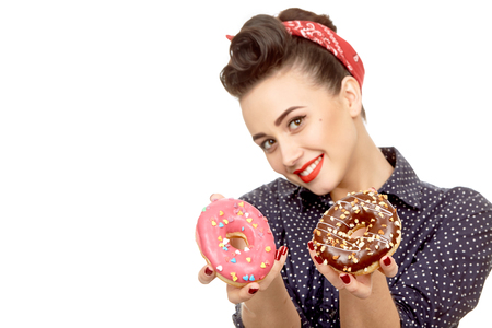Delicious addiction. Closeup shot of a gorgeous young pinup girl in a dotted retro dress and a headband smiling seductively holding out two tasty donuts isolated on white Stock Photo