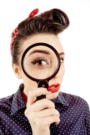 Kleine spion. Close-up studio shot van een mooie retro pinup meisje draagt een gestippelde jurk en een bandana kijkt door het vergrootglas met haar mond open in verrassing Stockfoto