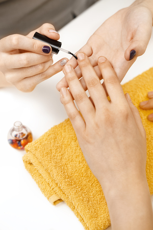 Preparing nails. Closeup shot of a manicurist pushing client cuticle back