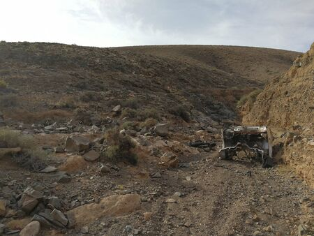 arid apocalyptic wasteland with the remains of an abandoned car