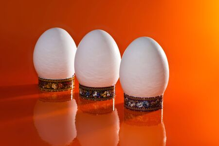 product range: A number of white eggs on the orange glossy background Stock Photo