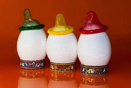 condones: Un n�mero de huevos blancos sobre un fondo de color naranja con los condones multicolores