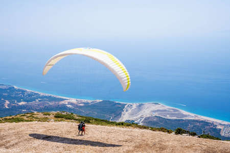 Paraglider is starting. Parachute is filling with air in the mountains alps on a sunny day in albania Imagens